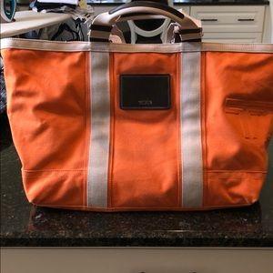 Orange & cream colored canvas Tumi tote bag
